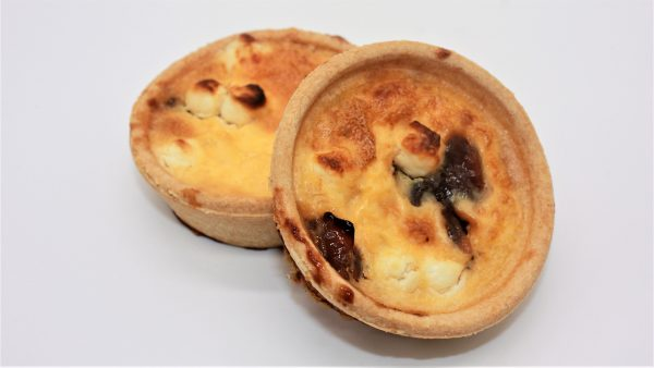 autumn caramalised red onion and goats cheese mini quiches white background