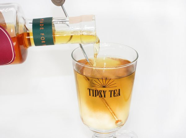 tea pouring into branded glass with stirrer