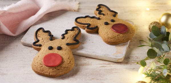 reindeer gingerbread cookies on wooden background with baubles