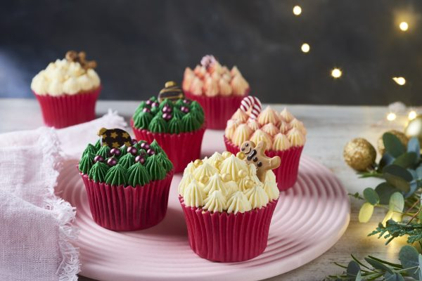 Christmas cupcakes on pink plate, chocolate gingerbread-man, baubles and candy-cain decoration on top