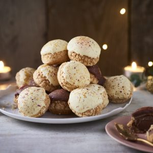profiteroles piles on a plate with lights, candles and