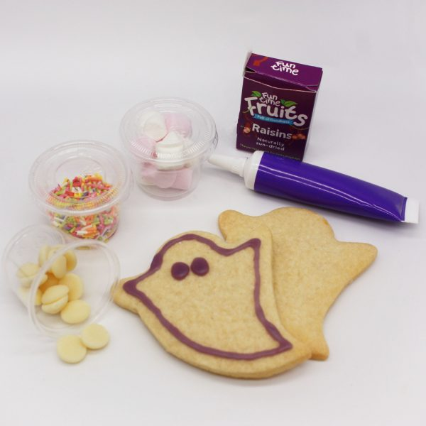 ghost cookies with sprinkles, marshmallows and white chocolate buttons and raisins on white background