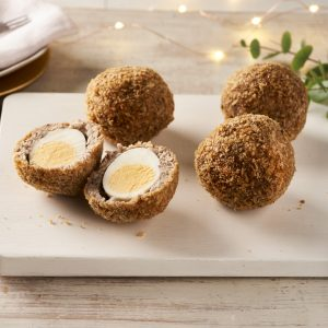 scotch eggs on board, one cut open with lights and leaves