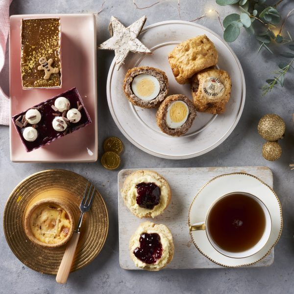 scotch eggs, susasage rolls and cakes on plate with star and baubles with christmas lights