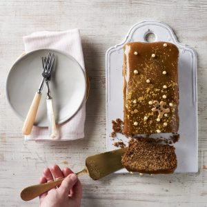 toffee covered loaf cake with slice cut out, a hand holding cake slice and a plate with cake forks on