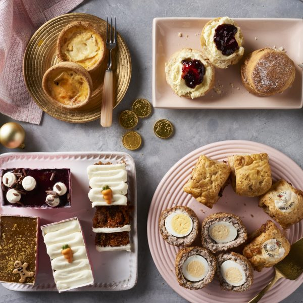 scotch eggs, scones, cakes, sausage rolls and quiches on plates with chocolate coins, pink napkins and a gold bauble